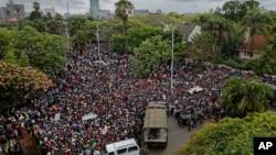 Une foule de milliers de manifestants demandant la démission du président Robert Mugabe se réunit derrière un cordon de l'armée sur la route menant à State House à Harare, Zimbabwe, 18 novembre 2017.