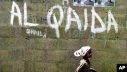 A girl walks past a wall with graffiti about the al-Qaida network in a Muslim area of the northern city of Kano, Nigeria. (File).