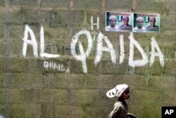 FILE - A girl walks past a wall with graffiti about the al-Qaida network in the northern city of Kano, Nigeria.