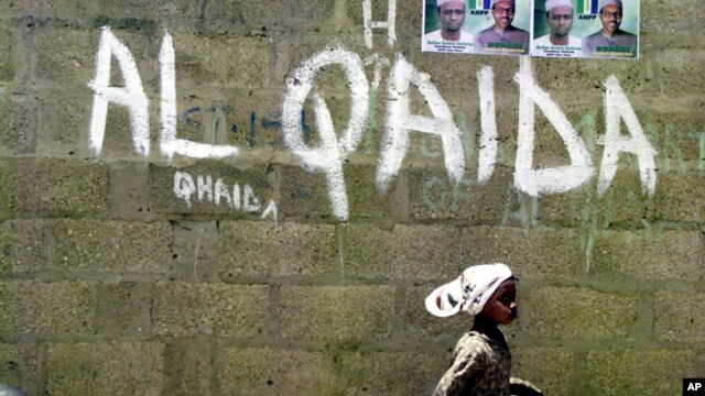 FILE - A girl walks past a wall with graffiti about the al-Qaida network in a Muslim area of the northern city of Kano, Nigeria.