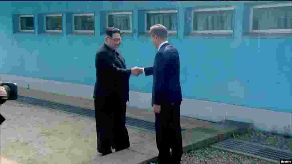 មេដឹកនាំកូរ៉េខាងជើង លោក Kim Jong Un ចាប់រលាក់ដៃជាមួយប្រធានាធិបតីកូរ៉េខាងត្បូងលោកMoon Jae-in នៅឯព្រំដែន គ្រាដែលភាគីទាំងពីរបានទៅដល់ទីកន្លែងសម្រាប់ជំនួបកំពូល នៅភូមិ Panmunjomដែលកិច្ចព្រមព្រៀងបញ្ចប់សង្គ្រាមកូរ៉េជាបណ្តោះអាសន្ន បានធ្វើឡើង។ រូបភាពនេះ ថតចេញពីវីដេអូ នៅកូរ៉េខាងត្បូង នៅថ្ងៃទី ២៧ ខែមេសា ឆ្នាំ២០១៨។
