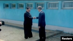 North Korean leader Kim Jong Un shakes hands with South Korean President Moon Jae-in at the concrete border as both of them arrive for the inter-Korean summit at the truce village of Panmunjom, in this still frame taken from video, South Korea April 27, 2018.