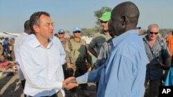 The U.N.'s top humanitarian official in South Sudan, Toby Lanzer (L), who was expelled from the country, visits displaced persons at a U.N. compound in 2013.