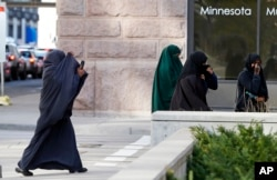 FILE - Female members of Minnesota's Somali community cover their faces as they arrive on April 23, 2015, for a hearing in federal court in St. Paul, Minnesota, in the case of several Minnesotans accused of plotting to travel to Syria to join the Islamic State group.