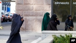 FILE - Female members of Minnesota's Somali community cover their faces as they arrive April 23, 2015, for a detention hearing in federal court in St. Paul in the case of Minnesotans accused of plotting to travel to Syria to join the Islamic State group.