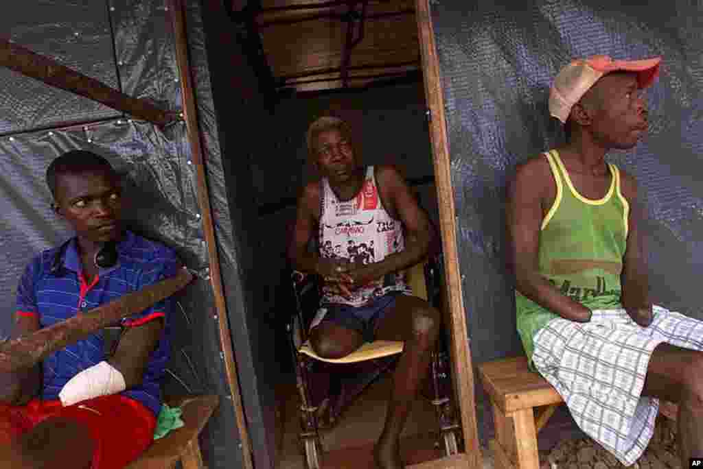 Sierra Leonean Nethaniel Bemeh, 72, center, who said his leg was shot off at point blank range by terrorist rebels, sits with his neighbors Abubakar Karbu, left, and David Kaiwo, right, who had hands chopped off by rebels, in front of their plastic shelte