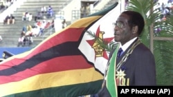 Zimbabwean President Robert Mugabe, sings the national anthem with the national flag in the background during Independence celebrations in Harare, Zimbabwe, Friday, April 18, 2003.