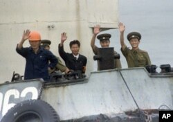 FILE - North Korean port officials wave from their launch as it approaches a South Korean ship near Yanghwa, North Korea, Aug. 19, 1997. Outsiders had been permitted to enter North Korea to attend a groundbreaking for construction of two light water nuclear reactors funded and built by South Korea, the U.S. and Japan. Then and in earlier years, North Korea was expanding economic relations with the West.