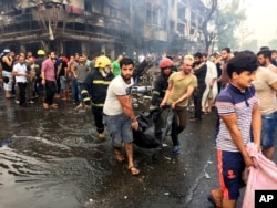 Iraqi firefighters and civilians carry bodies of victims killed in a car bomb at a commercial area in Karrada, Baghdad, July 3, 2016.