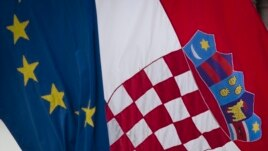 A Croatian, right, and a EU flag fly in downtown in Zagreb, Croatia, Sunday, Jun. 30, 2013.