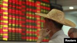 一名海南海口市的投資者在觀看股市的看板。