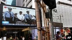 香港街头电视新闻屏幕显示检察人员把薄熙来押上法庭受审