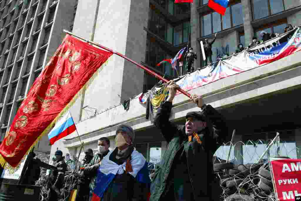 Activists wave an old Soviet and Russian national flags at a government building, in Donetsk, Ukraine.