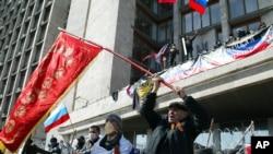 4月7日在烏克蘭東部的頓涅茨克,活動人士在一座政府辦公樓前揮舞前蘇聯和俄羅斯的國旗