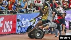 Seorang juru kamera menabrak pelari Usain Bolt saat merayakan kemenangan dalam nomor lari 200 meter, pada Kejuaraan Atletik Dunia di Beijing Kamis (27/8).
