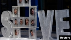Blocks of ice with pictures of 30 people arrested in Russia for protesting Arctic oil drilling dispayed outside Gazprom offices, Berlin, Nov. 14, 2013.
