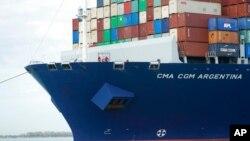 Miembros de la tripulación del CMA CGM Argentina, el barco carguero más grande en hacer escala en el Puerto de Miami, miran desde la proa el 6 de abril de 2021.
