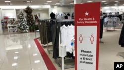 A social-distancing sign reminds shoppers to stay apart as a Christmas trees display stands at the end of walkway in a Macy's department store Thursday, Oct. 1, 2020, in northeast Denver. (AP Photo/David Zalubowski)