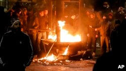 Protesters warm up next to a burning kiosk after minor clashes erupted during a protest in Bucharest, Romania, Feb. 2, 2017.