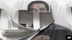A torn banner of former Tunisian President Zine El Abidine Ben Ali is seen in the center of Tunis, 16 Jan 2011