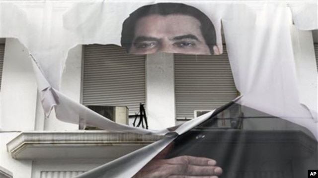 A torn banner of former Tunisian President Zine El Abidine Ben Ali is seen in the center of Tunis, 16 Jan 2011