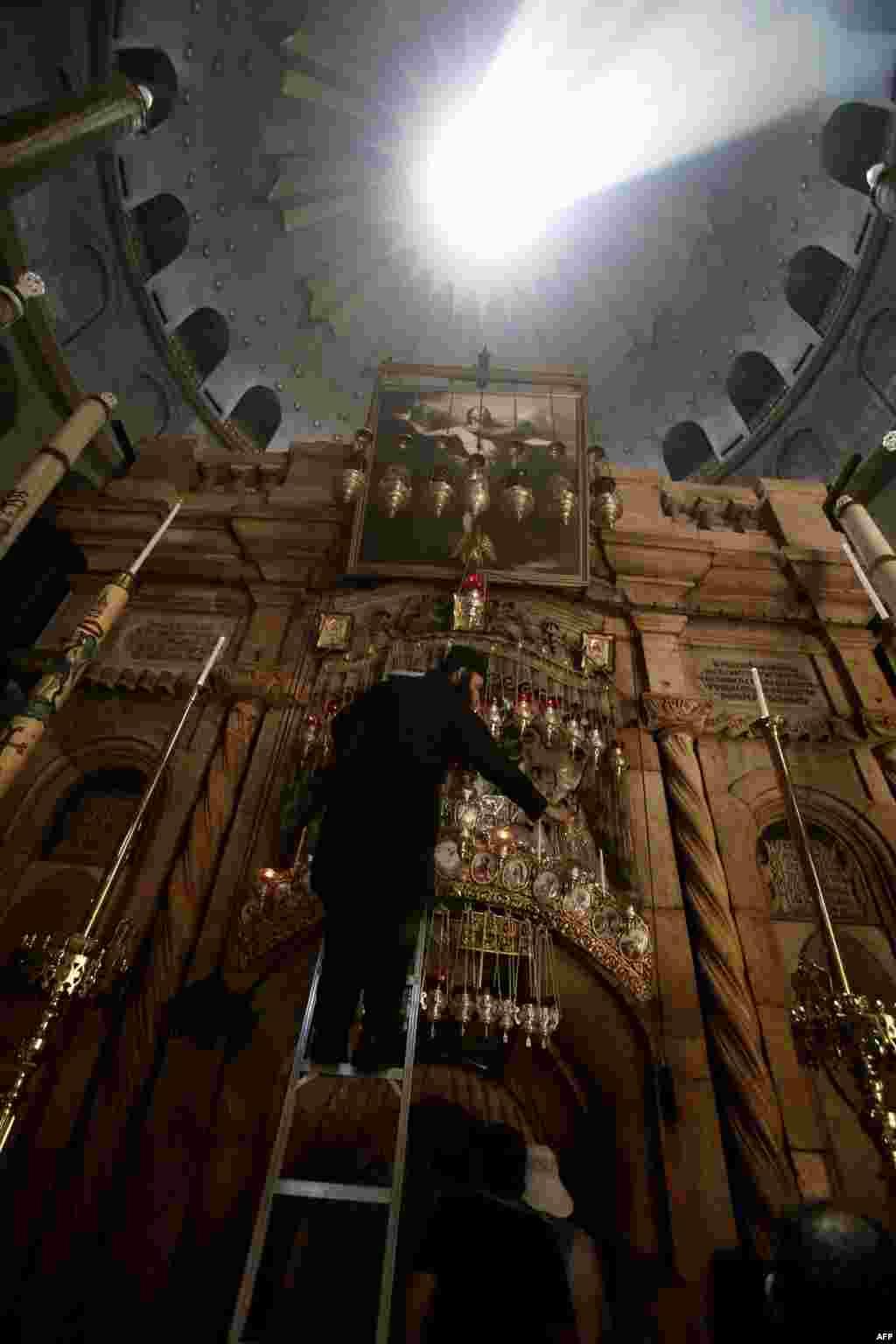 가톨릭 프란치스코 교황이 예루살렘 구시가지를 방문할 예정인 가운데, 예수 그리스도의 무덤 장소에 세워진 교회에서 그리스정교회 사제가 등에 불을 붙이고 있다.