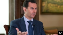 FILE - In this Wednesday, Sept. 21, 2016 photo released by the Syrian Presidency, Syrian President Bashar Assad speaks to The Associated Press at the presidential palace in Damascus, Syria.