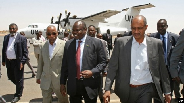 A delegation from South Sudan, headed by Pagan Amum, center, walks with Sudan's Idris Mohamed Abdul-Gadir, right, after their arrival in Khartoum, Sudan, (March 22, 2012 file photo)