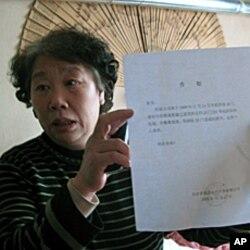 张安的妻子张学英举着强拆通知书