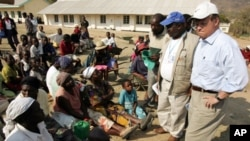 Then-US Ambassador to the UN food agency Tony Hall speaks to Zimbabwean villagers waiting to collect food aid near Mutare, Zimbabwe in this August 2005 file photo.