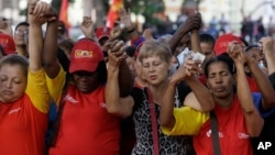 People pray during a demonstration in support of Venezuela's President Hugo Chavez at the Simon Bolivar Square in Caracas, Venezuela, Sunday, Dec. 9, 2012.