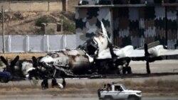 ماموران امنیتی از کنار لاشه یک هواپیما در پایگاه نیروی دریایی در کراچی عبور می کنند، ۲۳ مه ۲۰۱۱