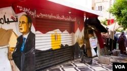"""一家埃及教堂门口的商店上挂有""""国家,军事,警察,穆斯林和基督徒都是一家""""的横幅(2017年5月20日)"""