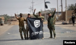 FILE - Shi'ite Popular Mobilization Forces (PMF) fighters remove an Islamic State flag after liberating the city of Al-Qaim, Iraq, Nov. 3, 2017.