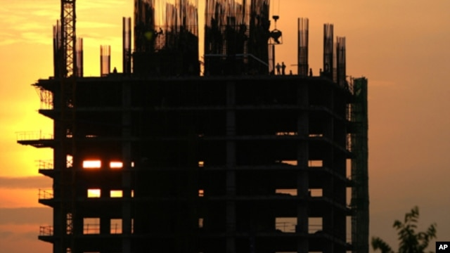 Construction workers work on a new building in Phnom Penh. Cambodia is embracing a thriving real estate market, where land and housing prices in the capital city skyrocket with no sign of letting up, file photo.