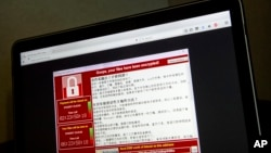 FILE - Screenshot of the warning screen from a purported ransomware attack, as captured by a computer user in Taiwan, is seen on laptop in Beijing, May 13, 2017.