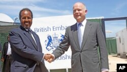 British Foreign Secretary William Hague, right, shakes hands with Somali President, Hassan Sheikh Mohamud, at the opening of the newly built British Embassy in the Somali capital Mogadishu, Apr. 25, 2013.