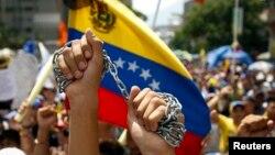 En Caracas, un manifestante marcha con una cadena en alto en señal de que el Gobierno tiene encadenados a los trabajadores