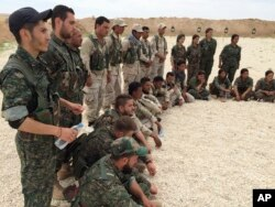 FILE - In this file photo taken May 21, 2016, members of what the U.S. calls the Syrian Democratic Forces gather after a training session at a firing range in northern Syria.