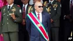 FILE - Suriname President Desire Delano Bouterse observes a military parade, after being sworn in for his second term, in Paramaribo, Suriname, Aug. 12, 2015
