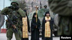 Orthodox monks pray next to armed servicemen near Russian army vehicles outside a Ukrainian border guard post in the Crimean town of Balaclava March 1, 2014.