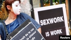 一名戴着面具的妓女举着标语牌参加示威,抗议法国里昂取缔卖淫提案。(2012年7月6日)