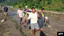Nepalese villagers carry a landslide survivor in the Kaski district of western Nepal on July 30, 2015. Landslides triggered by heavy rains killed at least 24 people on July 30 and left more than a dozen missing as homes were swept away in three districts