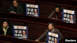 Pro-democracy lawmakers display portraits of Lee Bo, one of the five booksellers who disappeared from a local bookstore, as Chief Executive Leung Chun-ying speaks during his annual policy address at the Legislative Council in Hong Kong, Jan. 13, 2016. The