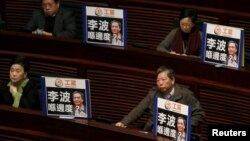 "FILE - Pro-democracy lawmakers display portraits of Lee Bo, one of the five booksellers who disappeared from a local bookstore, as Chief Executive Leung Chun-ying speaks during his annual policy address at the Legislative Council in Hong Kong, Jan. 13, 2016. The Chinese characters on the placards read, ""Where is Lee Bo?"""