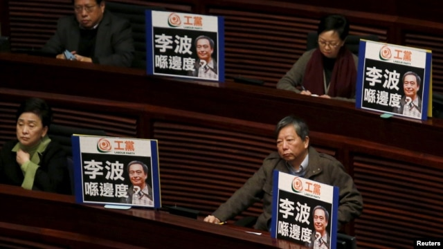 """FILE - Pro-democracy lawmakers display portraits of Lee Bo, one of the five booksellers who disappeared from a local bookstore, as Chief Executive Leung Chun-ying speaks during his annual policy address at the Legislative Council in Hong Kong, Jan. 13, 2016. The Chinese characters on the placards read, """"Where is Lee Bo?"""""""