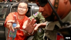 Cambodian opposition Senator Hong Sok Hour (L) of the Sam Rainsy Party (SRP) is escorted by police officers at the Municipal Court in Phnom Penh, Cambodia, 02 October 2015.