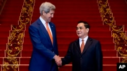 2016年1月25日在老挝首都万象,到访的美国国务卿克里与老挝总理通辛·坦马冯握手。