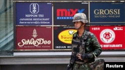 A soldier stands guard outside a shopping mall to stop protests against military rule at a shopping district in central Bangkok, June 1, 2014.