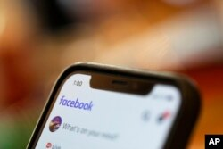 FILE - An iPhone displays a Facebook page, Aug. 11, 2019. Facebook said March 24, 2021, that hackers in China had used fake accounts and impostor websites in a bid to break into the phones of Uyghur Muslims.